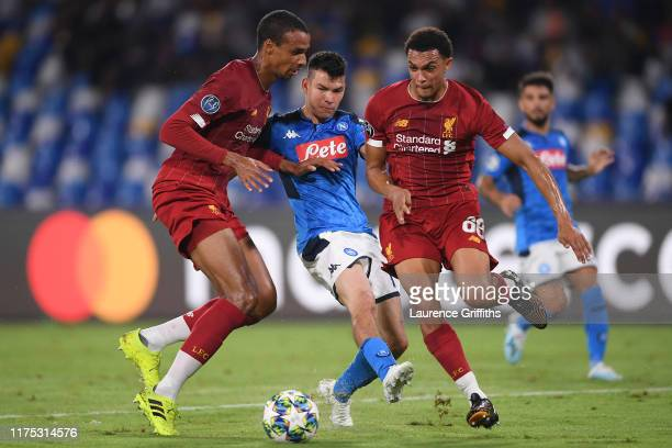 Hirving Lozano of Napoli battles with Joel Matip and Trent AlexanderArnold of Liverpool during the UEFA Champions League group E match between SSC...