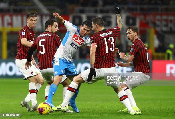 Hirving Lozano of SSC Napoli competes for the ball with Giacomo Bonaventura and Alessio Romagnoli of AC Milan during the Serie A match between AC...