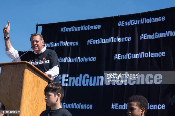 His arm raised, American activist Father Michael Pfleger, of St Sabina Church, speaks from the stage, during an End Gun Violence rally, Washington...