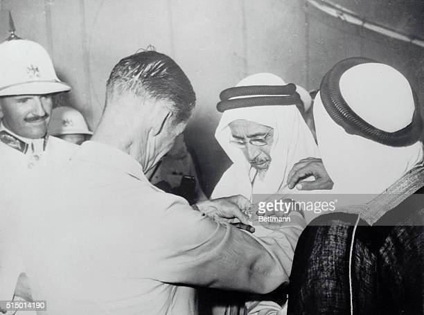 His bespectacled highness Sheik Ali Bin Abdulla Al Thani ruler of Qatar an Arab state in the Indian Ocean looks down at the insignia of a Knight...
