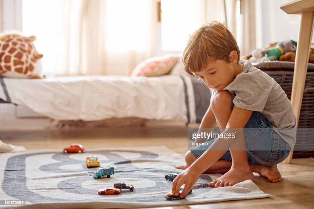 His cars is his favorite thing to play with : Stock Photo