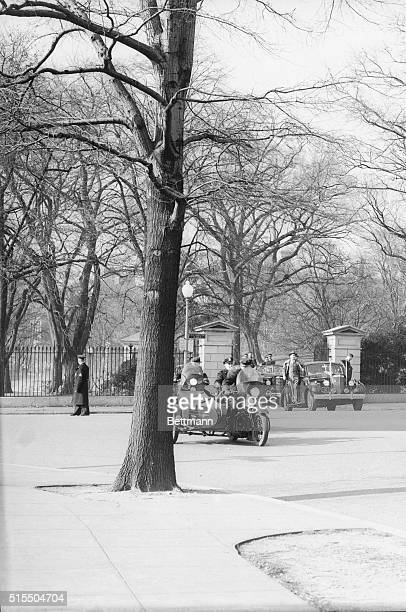 His closed car heavily guarded by secret service men in accompanying cars and along running boards of his car President Franklin D Roosevelt leaves...