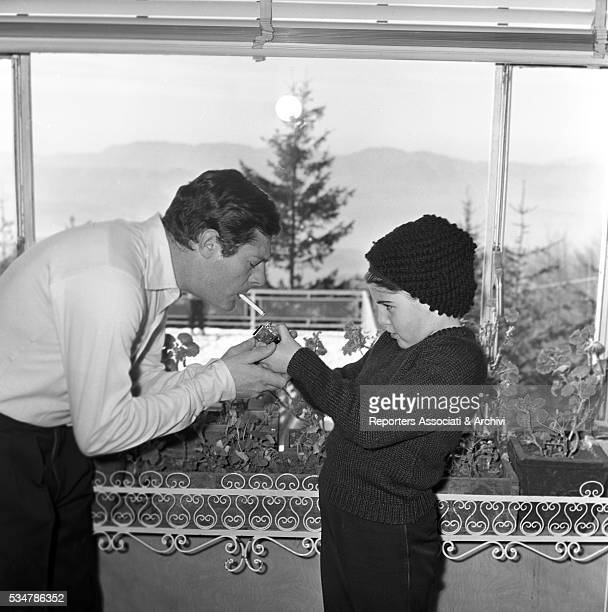 His daughter Barbara lighting a cigarette for his father and Italian actor Marcello Mastroianni touching h's chin during their holiday in a village...