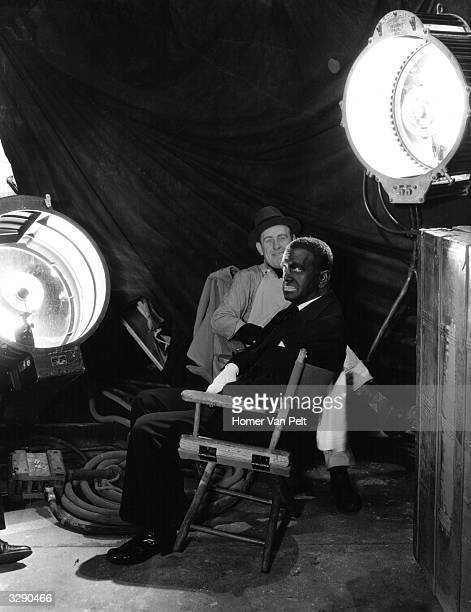 His face covered in his trademark black makeup Al Jolson relaxes on the set of the Warner Brothers musical 'Go Into Your Dance' directed by Archie...