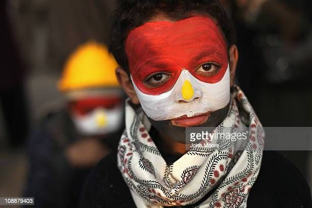 His face painted in the national colors antigovernment protester Mamoud Tariq attends a demonstration in Tahrir Square on February 7 2011 in Cairo...