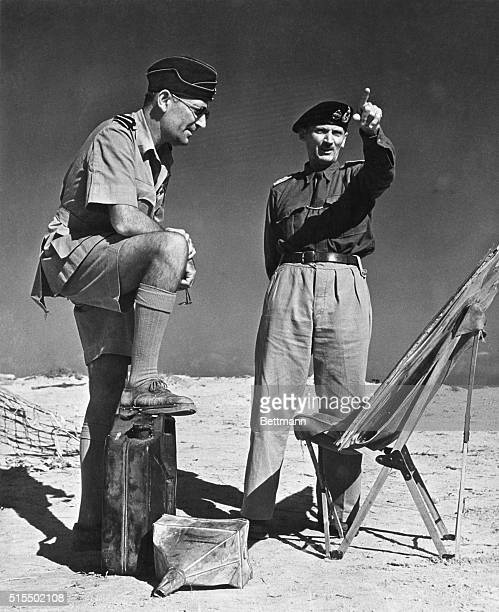 His foot on a captured fuel can of the Afrika Korps Air Vice Marshall Arthur Coningham air officer commanding the western desert makes his report to...
