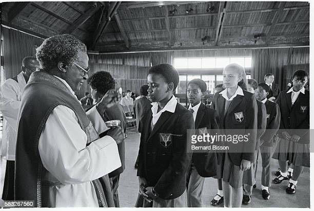 His Grace Desmond Tutu Nobel Peace Prize winning Anglican bishop gives children holy communion as he says mass in the SaintBarnabus church of Bosmont