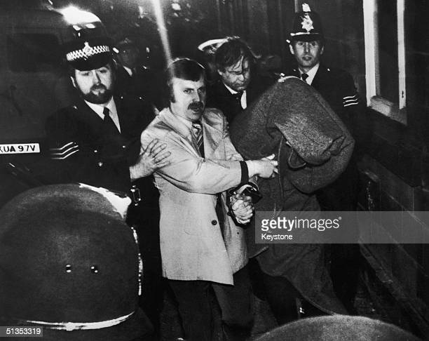 His head covered with a blanket, Peter Sutcliffe, aka 'The Yorkshire Ripper', is escorted into Dewsbury Magistrates Court to be charged with murder,...