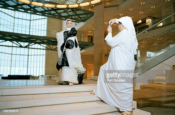 His Highness the Emir Sheikh Hamad bin Khalifa Al Thani photographs his wife Sheikha Mozah bint Nasser alMissned inside the new Museum of Islamic Art...