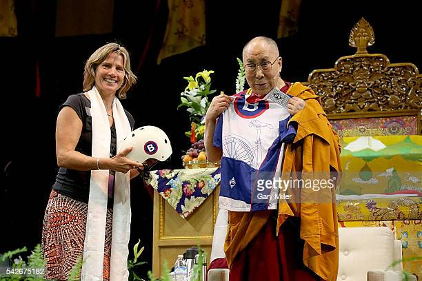 His Holiness the 14th Dalai Lama is presented with a bicycle helmet and jersey by Boulder Mayor Suzanne Jones during A Teaching The Eight Verses of...