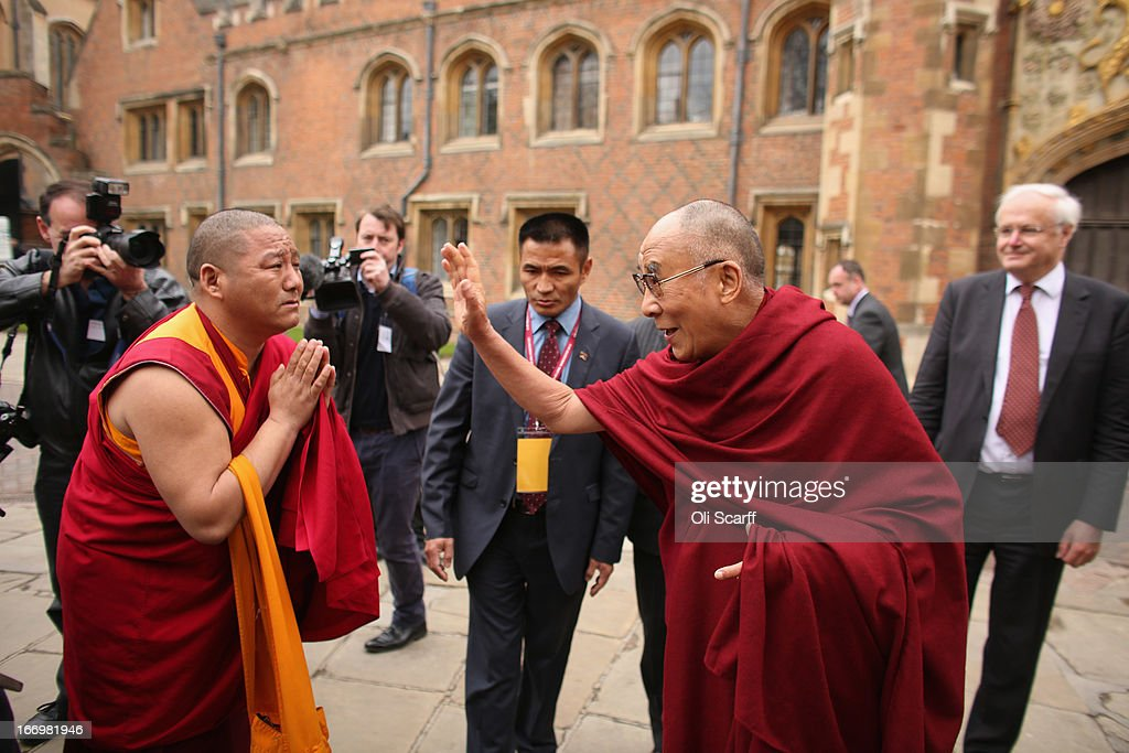 His Holiness the Dalai Lama (2nd R) blesses a man wearing Buddhist robes as he arrives to attend a press conference in the Divinity School of St. John's College, part of the University of Cambridge, on April 19, 2013 in Cambridge, England. The Dalai Lama was invited to address an audience in St. John's College by the Global Scholars Symposium during his 5-day visit to the UK. The exiled 77 year-old Buddhist Tibetan leader spoke on themes of non-violence, compassion, dialogue and universal responsibility.