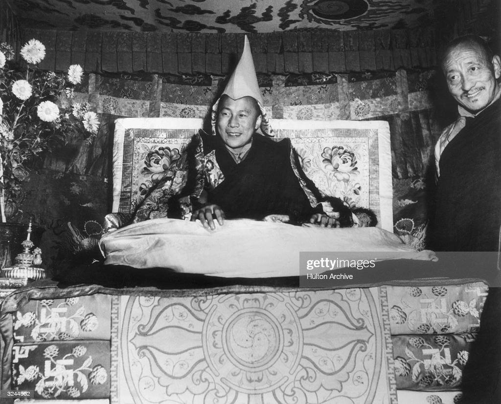 His Holiness the Dalai Lama, Tenzin Gyatso, seated on his throne and wearing the gold peaked cap which is his Crown, smiles while giving an audience in Lhasa, Tibet. An assistant monk stands at his side.