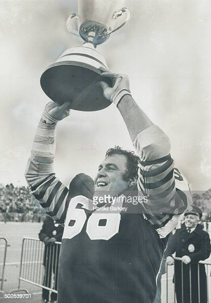 His last game: Angelo Mosca shows off the Grey Cup to the delight of the roaring Hamilton fans yesterday at Ivor Wynne Stadium. For Big Angie; it was...
