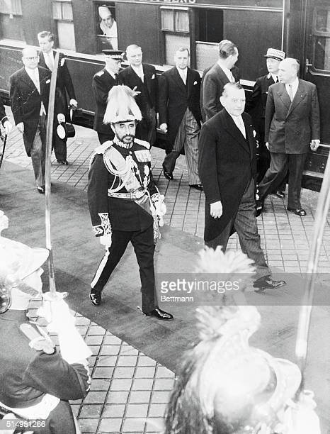 His majesty Haile Selassie Emperor of Ethiopia is shown in field marshal's uniform and plumed helmet walking with President Rene Coty of France who...