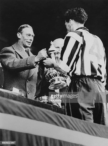 His Majesty King George VI presents Newcastle United captain Joe Harvey with the Football Association Challenge Cup after defeating Blackpool 2 0...