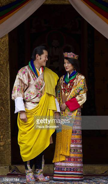 His majesty King Jigme Khesar Namgyel Wangchuck holds his Raven crown as he and the Queen Jetsun Pema walk out after their marriage ceremony is...