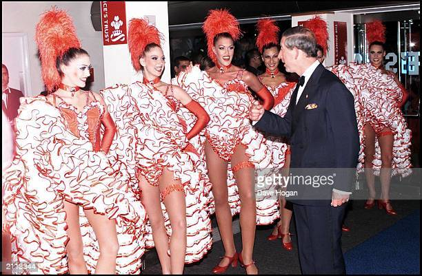 His Royal Highness prince Charles is greeted by a line of cancan dancers as he arrives at the Empire Cinema in London on September 3 2001 for the UK...