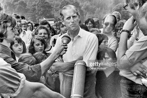 His Royal Highness, Prince Philip, the Duke of Edinburgh pictured surrounded by a crowd of onlookers as he answers questions from television...