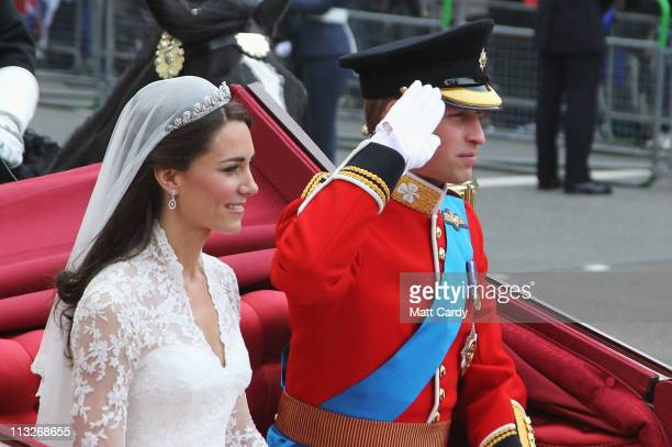 His Royal Highness Prince William Duke of Cambridge salutes next to Catherine Duchess of Cambridge as they make the journey by carriage procession to...