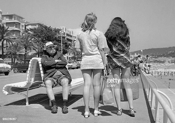 his trousers' legs rolled to take advantage of the sun a retired man looks toward two girls wearing miniskirt 13 July 1969 in Nice