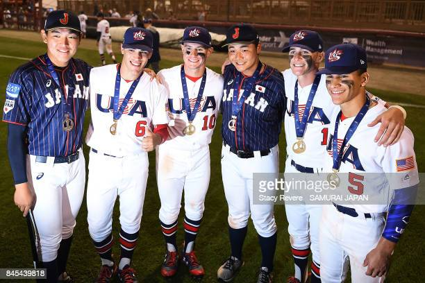 Hisanori Yasuda and Kotaro Kiyomiya of Japan pose for pictures with members of the USA National team following the WBSC U18 Baseball World Cup Medal...