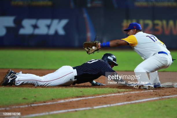 Hisanori Yasuda of Japan returns safely into first base against Jair Camargo of Colombia in the 3rd inning during the WBSC U23 World Cup Group A...