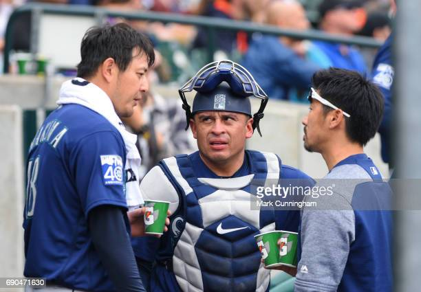 Hisashi Iwakuma and Carlos Ruiz of the Seattle Mariners talk to each other through interpreter Antony Suzuki in the dugout at the end of the third...