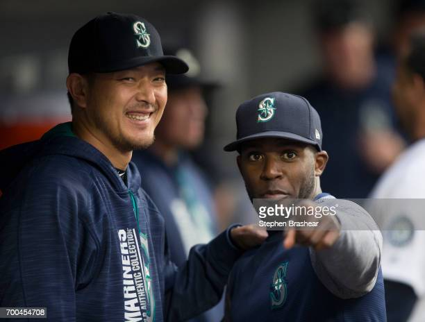 Hisashi Iwakuma left of the Seattle Mariners and Guillermo Heredia of the Seattle Mariners pose for a photo in the dugout before a game against the...