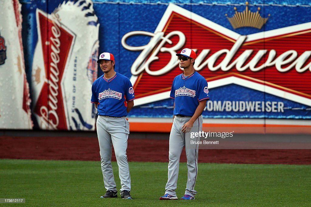 Hisashi Iwakuma of the Seatle Mariners and Yu Darvish of the Texas Rangers stand in the outfield during Gatorade All-Star Workout Day on July 15, 2013 at Citi Field in the Flushing neighborhood of the Queens borough of New York City.