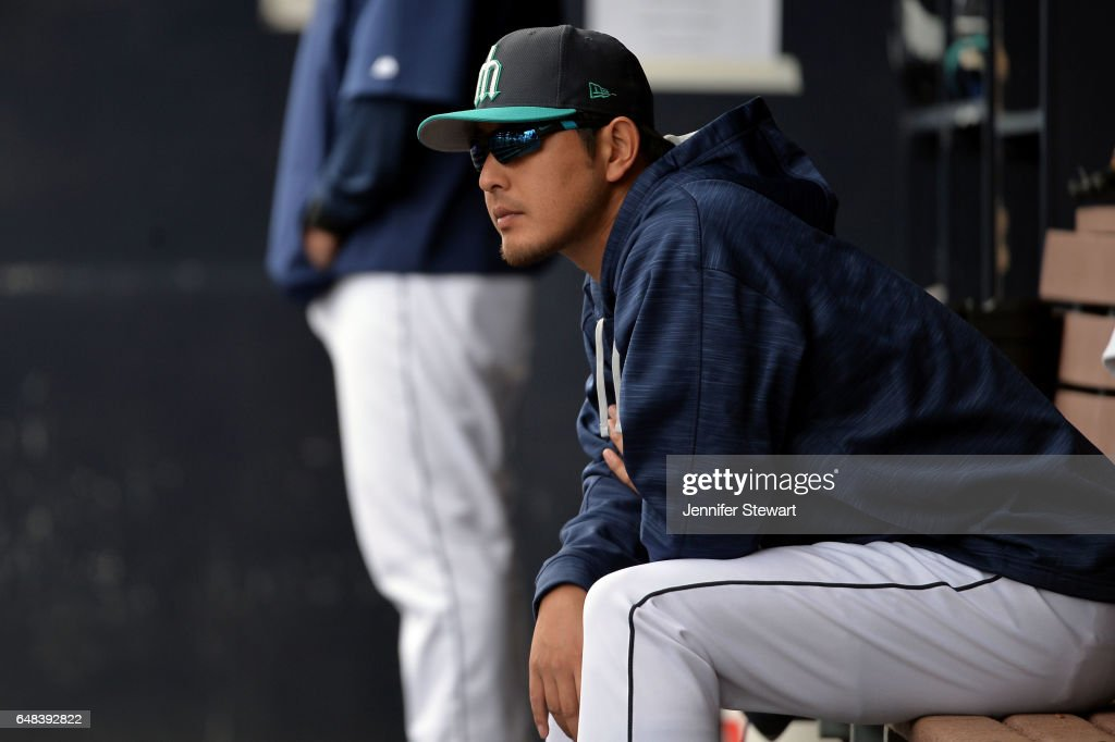 Hisashi Iwakuma #18 of the Seattle Mariners sits in the dugout during the second inning of the spring training game against the Oakland Athletics at Peoria Stadium on March 5, 2017 in Peoria, Arizona.