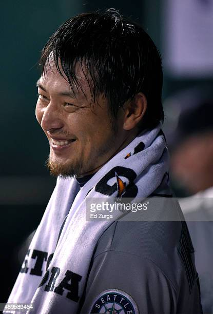 Hisashi Iwakuma of the Seattle Mariners smiles as he watches from the dugout after pitching in the fifth inning against the Kansas City Royals at...