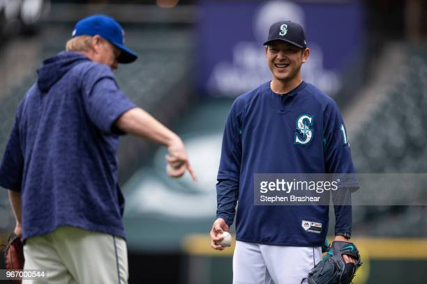 Hisashi Iwakuma of the Seattle Mariners smiles while talking with Seattle Mariners pitching coach Mel Stottlemyre before a game against the Tampa Bay...