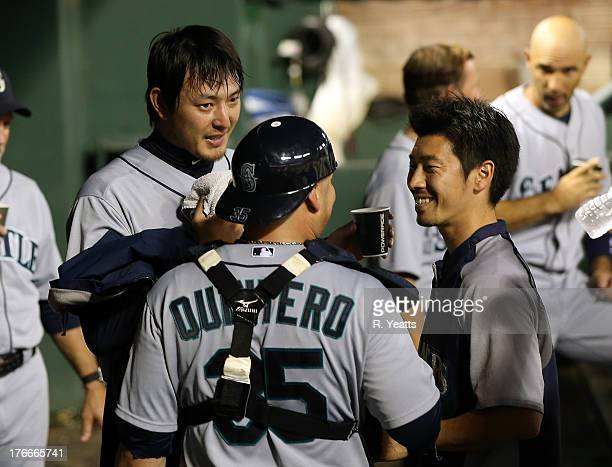 Hisashi Iwakuma talks with his translator and catcher Humberto Quintero of the Seattle Mariners between innings against the Texas Rangers at Rangers...