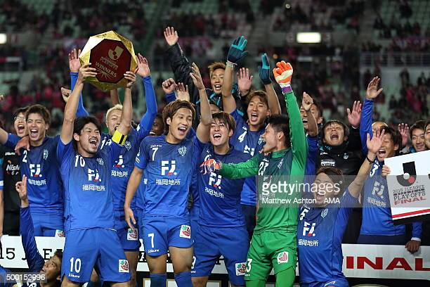 Hisashi Jogo of Avispa Fukuoka lifts the J2 Play Off Winners trophy as his team celebrate promotion to J1 after the J1 Promotion Play Off Final...