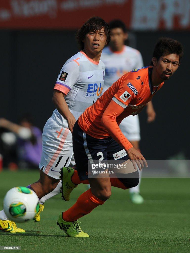 Hisato Sato #11 of Sanfrecce Hiroshima (L) and Kosuke Kikuchi #2 of Omiya Ardija compete for the ball during the J.League match between Omiya Ardija and Sanfrecce Hiroshima at Nack 5 Stadium Omiya on May 6, 2013 in Saitama, Japan.