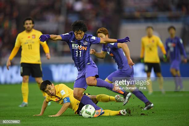 Hisato Sato of Sanfrecce Hiroshima is tackled by Zheng Zhi of Guangzhou Evergrande FC during the FIFA Club World Cup 3rd Place Match between...