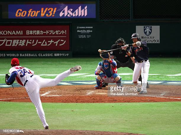 Hisayoshi Chono of Japan hits a RBI single in the top of ninth inning during the World Baseball Classic First Round Group A game between Japan and...