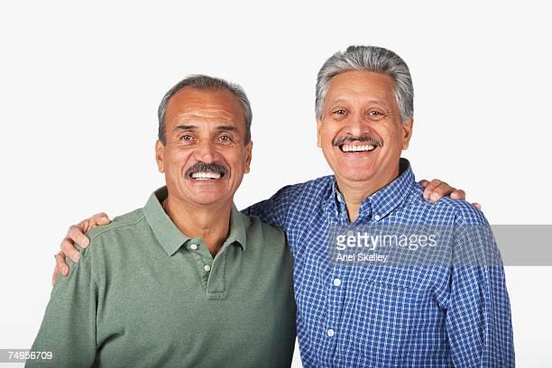 Hispanic adult brothers hugging