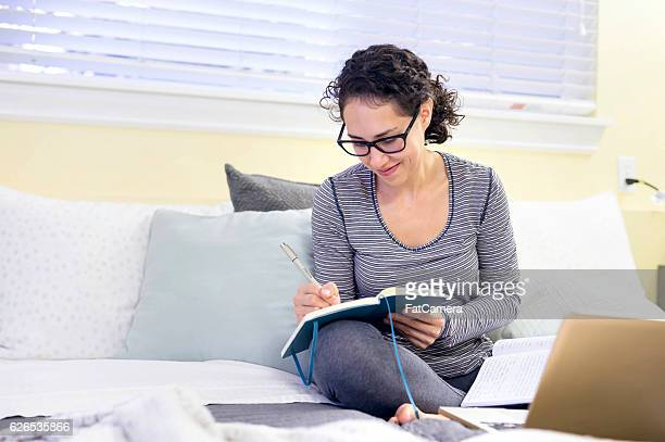 Hispanic adult female smiling while journaling over the weekend