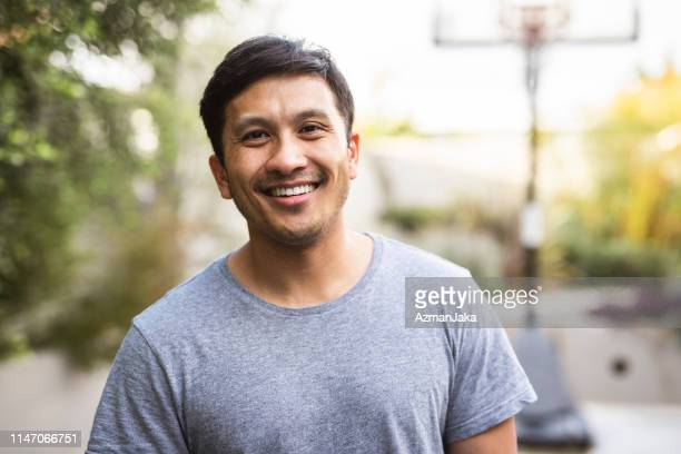 hispanic adult standing outside and smiling - latin american and hispanic ethnicity stock pictures, royalty-free photos & images