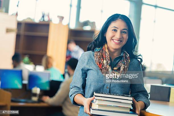 Hispanic adult student checking out books from college library
