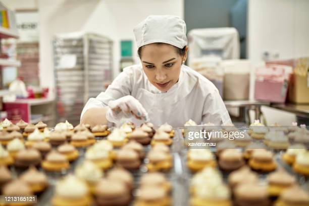 hispanic american female baker decorating vegan cupcakes - food and drink industry stock pictures, royalty-free photos & images