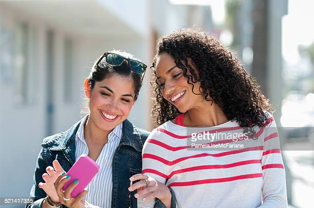 Hispanic and African American Girlfriends Laughing at Cellular Phone