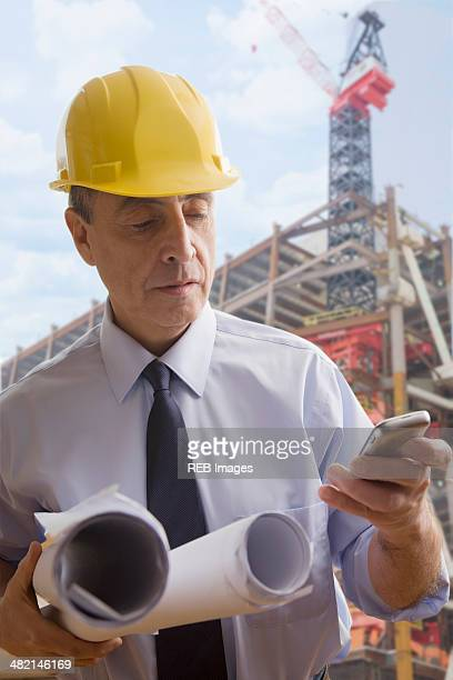 Hispanic architect using cell phone at construction site