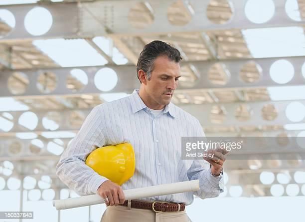 Hispanique avec plan de l'architecte sur le chantier de construction