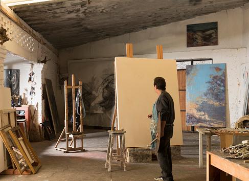 Hispanic artist painting in studio - gettyimageskorea