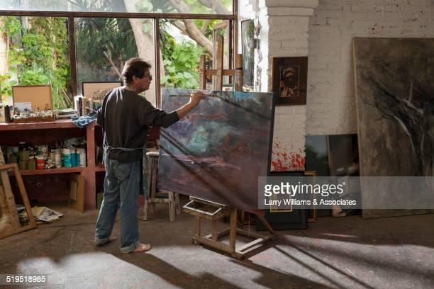 Hispanic artist painting in studio