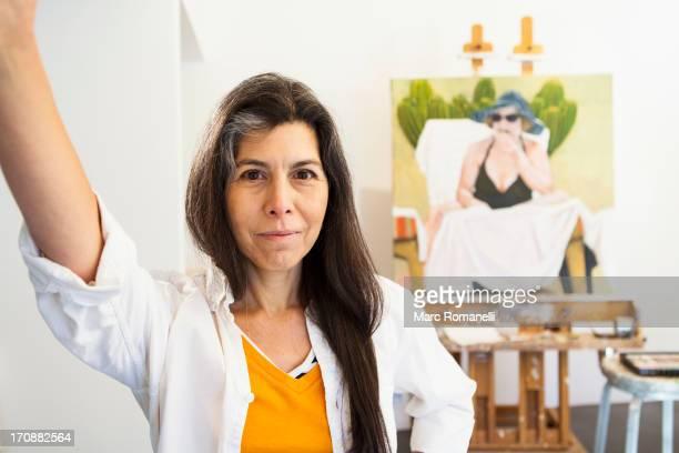Hispanic artist smiling in studio