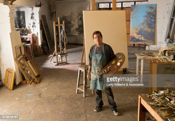 Hispanic artist standing in studio
