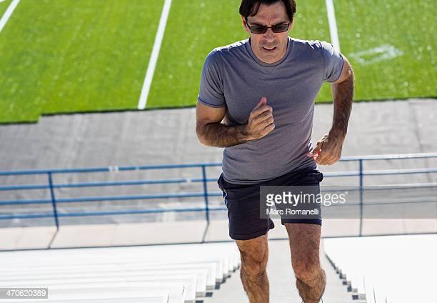 Hispanic athlete running on bleacher steps